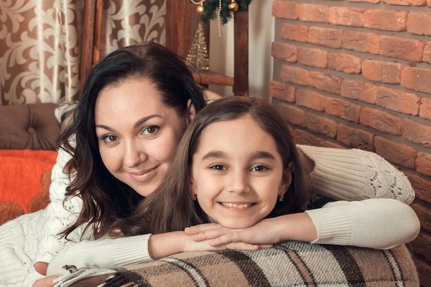 Deux jolies filles, mère et fille, s'installant sur un canapé dans une chambre décorée pour noël.