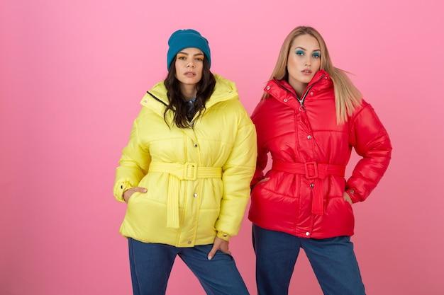 Deux jolies filles posant sur fond rose en veste d'hiver colorée de couleur rouge et jaune vif