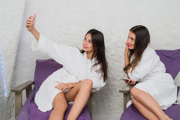 Deux jolies filles prenant selfie à l'aide de smartphone dans la salle de sel