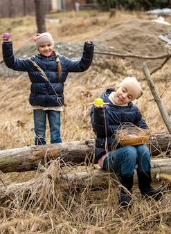 Deux jolies filles à la recherche d'oeufs de pâques en forêt