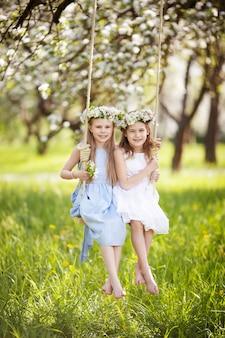 Deux jolies filles s'amusant sur une balançoire dans le vieux jardin de pommiers en fleurs. journée ensoleillée. activités de plein air printanières pour les enfants