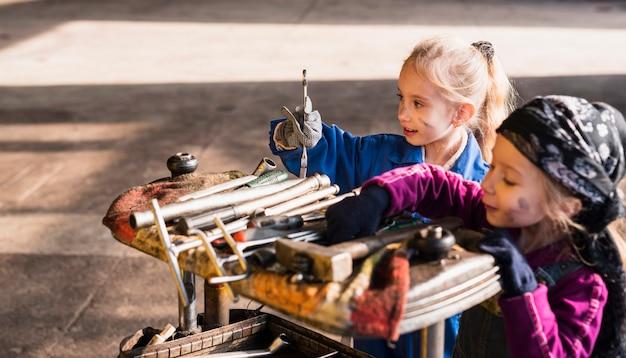 Deux jolies filles en salopette choisissant des outils