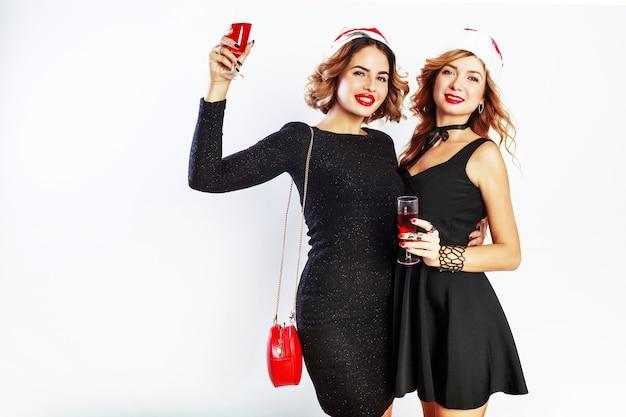 Deux jolies filles sexy en chapeau de vacances noël père noël rouge posant sur fond blanc, tenant un verre de vin.