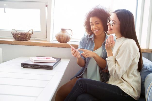 Deux jolies filles sont assises ensemble à la table. ils regardent le téléphone et sourient. les élèves s'amusent beaucoup ensemble.