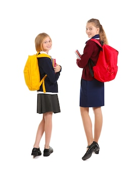 Deux jolies filles en uniforme scolaire sur une surface blanche