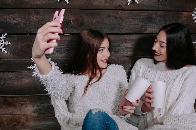 Deux jolies jeunes amies drôles de femmes souriantes et s'amusant, font salfie