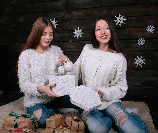Deux jolies jeunes amies drôles de femmes souriantes et s'amusant, tenant des cadeaux de vacances, prêtes pour la célébration.