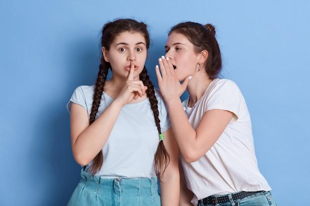 Deux jolies jeunes femmes aux cheveux noirs posant contre le mur bleu