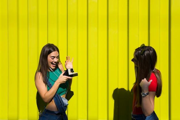 Deux jolies jeunes femmes heureuses prenant des photos avec un appareil photo rétro et passent un bon moment