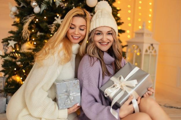 Deux jolies jeunes femmes heureuses soeurs avec un sourire dans des vêtements tricotés à la mode avec un pull et un chapeau tiennent des cadeaux sur fond d'arbre de noël et de lumières à la maison. vacances d'hiver