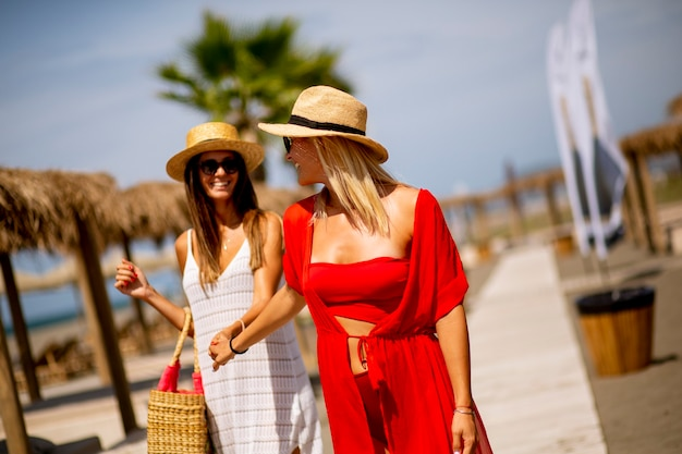 Deux jolies jeunes femmes marchant sur une plage en été