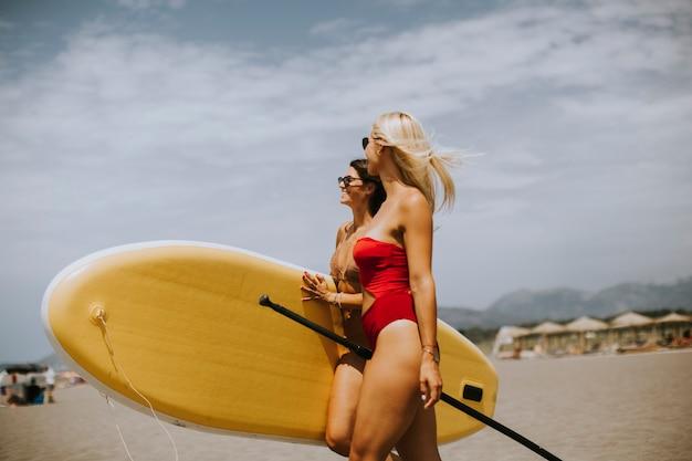 Deux jolies jeunes femmes avec paddle board sur la plage un jour d'été