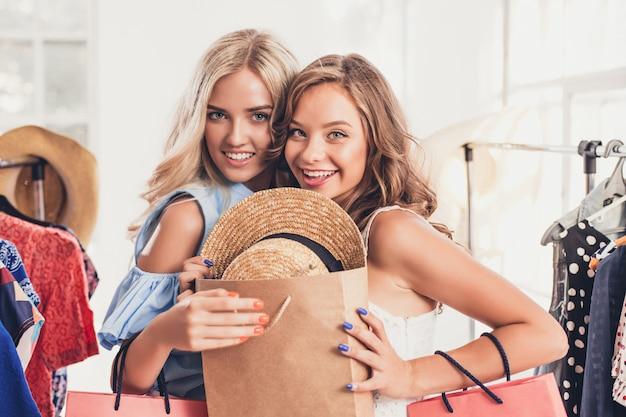 Les deux jolies jeunes femmes regardant des robes et l'essaient en choisissant en boutique