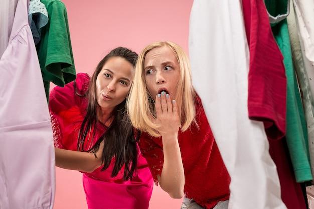 Les deux jolies jeunes femmes regardant des robes et l'essayent en choisissant au magasin