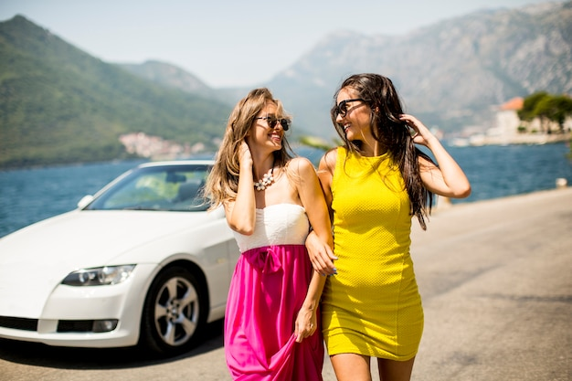 Deux jolies jeunes femmes en voiture cabriolet blanche sur le bord de la mer