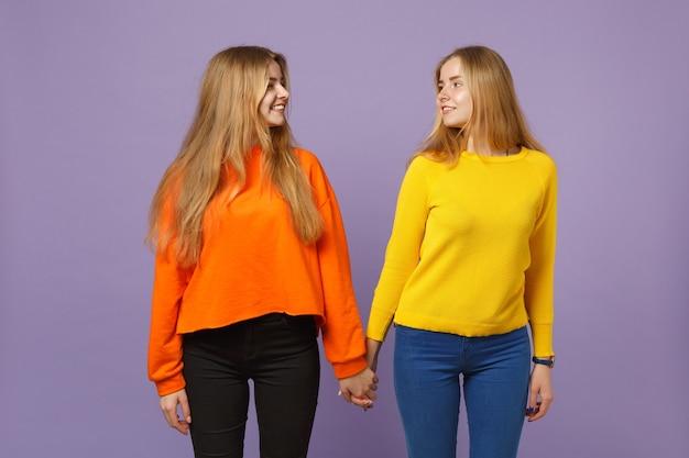 Deux jolies jeunes filles jumelles blondes dans des vêtements colorés se regardant isolées sur un mur bleu violet pastel. concept de mode de vie familial de personnes. .