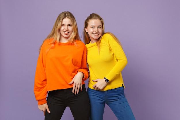 Deux jolies jeunes filles jumelles blondes dans des vêtements colorés vifs montrant la langue isolée sur un mur bleu violet pastel. concept de mode de vie familial de personnes.