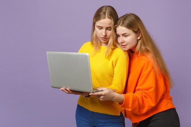 Deux jolies jeunes filles jumelles blondes dans des vêtements colorés vifs tenant, à l'aide d'un ordinateur portable isolé sur un mur bleu violet pastel. concept de mode de vie familial de personnes.