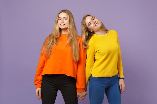 Deux jolies jeunes filles jumelles blondes souriantes dans des vêtements colorés vifs, isolées sur un mur bleu violet pastel. concept de mode de vie familial de personnes.