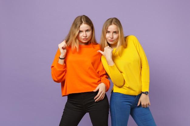 Deux jolies jeunes filles jumelles blondes vêtues de vêtements colorés vifs pointant les pouces de côté isolés sur un mur bleu violet pastel. concept de mode de vie familial de personnes. .