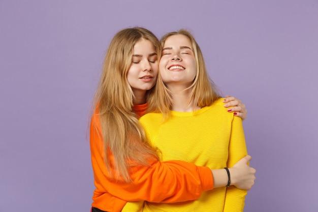 Deux jolies jeunes filles jumelles blondes vêtues de vêtements colorés vifs s'embrassant, gardant les yeux fermés isolés sur un mur bleu violet pastel. concept de mode de vie familial de personnes.