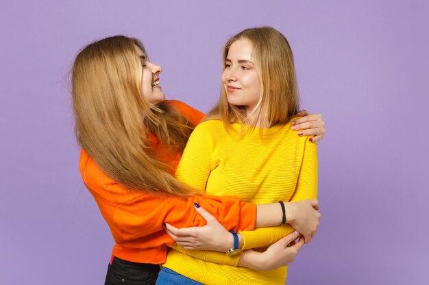 Deux jolies jeunes filles jumelles blondes vêtues de vêtements colorés vifs s'embrassant se regardant isolées sur un mur bleu violet pastel. concept de mode de vie familial de personnes.