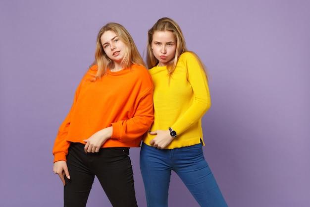 Deux jolies jeunes filles jumelles blondes vêtues de vêtements colorés vifs, soufflant des lèvres isolées sur un mur bleu violet pastel. concept de mode de vie familial de personnes.