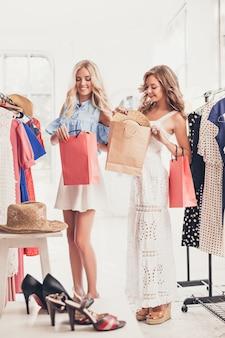 Les deux jolies jeunes filles regardant des robes et l'essayent en choisissant au magasin