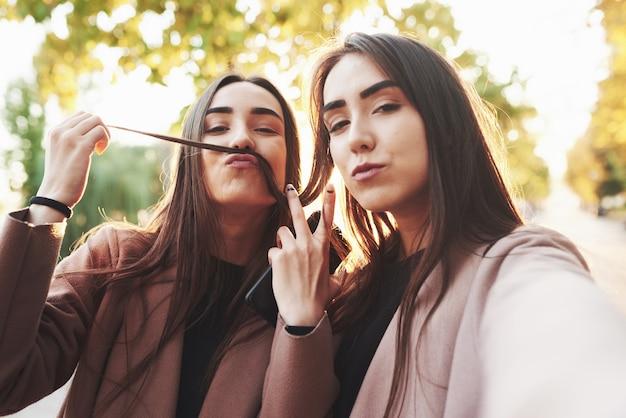 Deux jolies et jolies, jeunes filles jumelles brune en manteau décontracté s'amusant tout en prenant selfie et en jouant avec les cheveux, poussant le signe av en plein air dans un parc d'automne ensoleillé sur l'arrière-plan flou.