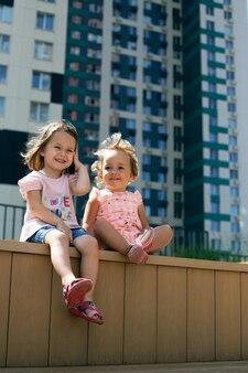 Deux jolies petites filles assises à l'extérieur dans un paysage urbain. génération alpha. format vertical, sœurs