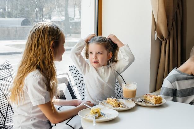 Deux jolies petites filles sont assises dans un café et jouent par une journée ensoleillée. loisirs et style de vie.