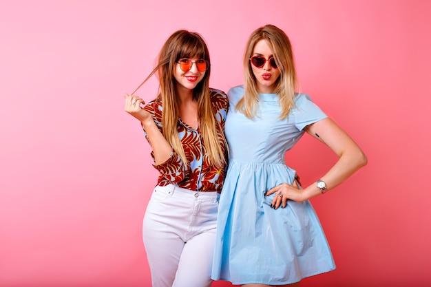 Deux jolies sœurs heureuses meilleures amies hipster femmes s'amusant ensemble au fond de studio rose
