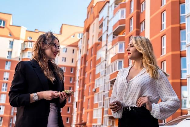 Deux jolis agents immobiliers tout en se tenant près d'une maison à vendre en plein air