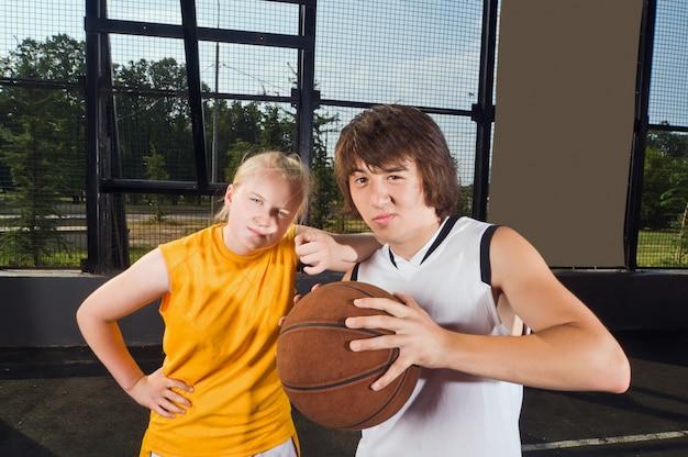 Deux joueurs de basket-ball adolescents posant