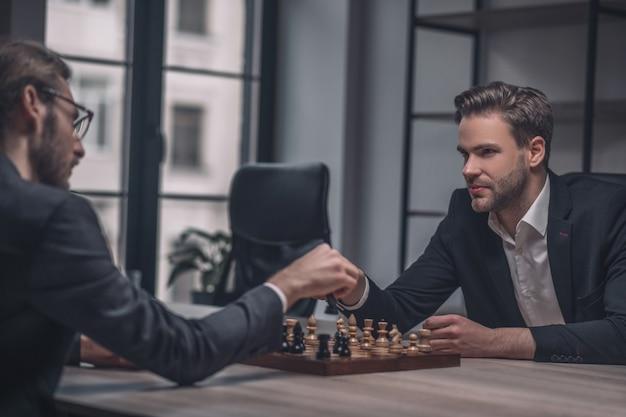 Deux joueurs impliqués dans des costumes d'affaires se tenant la main sur l'échiquier assis à table au bureau