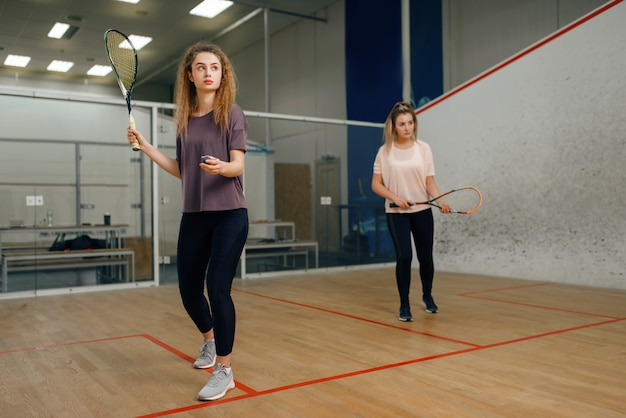 Deux joueurs avec raquette de squash jouant sur le court