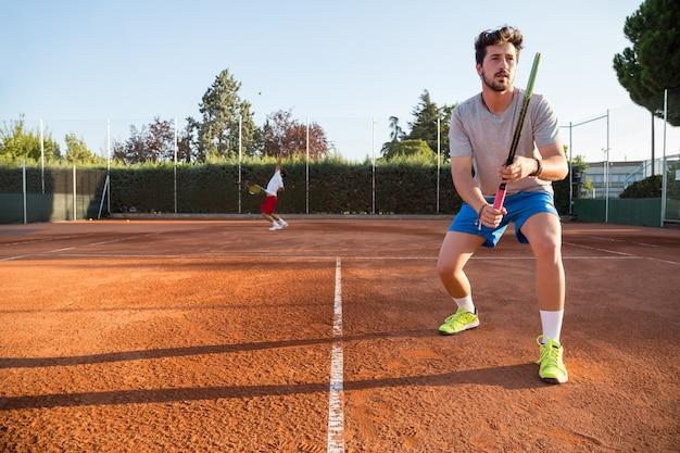 Deux joueurs de tennis professionnels en compétition contre une autre équipe.