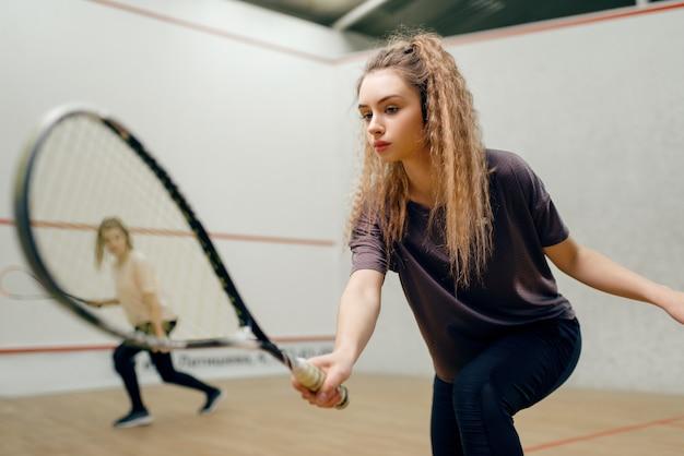 Deux joueuses avec raquette de squash jouant sur le court. fille sur la formation de jeu, passe-temps sportif actif, entraînement de remise en forme pour un mode de vie sain