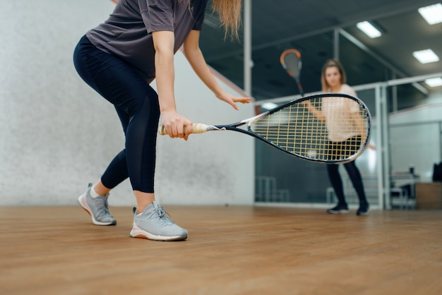 Deux joueuses avec raquettes, partie de squash sur le court. filles en formation, passe-temps sportif actif, entraînement de fitness pour un mode de vie sain