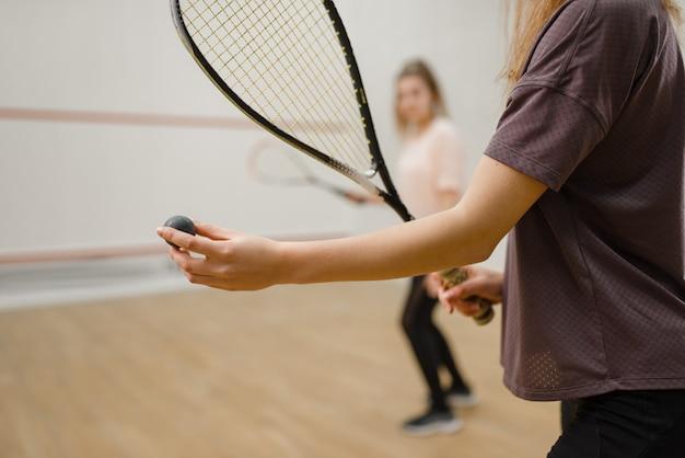 Deux joueuses avec des raquettes de squash, se concentrent sur la balle. filles en formation, passe-temps sportif actif, entraînement de fitness pour un mode de vie sain