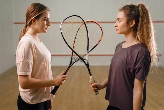 Deux joueuses avec des raquettes de squash se tiennent face à face. filles en formation, passe-temps sportif actif, entraînement de fitness pour un mode de vie sain