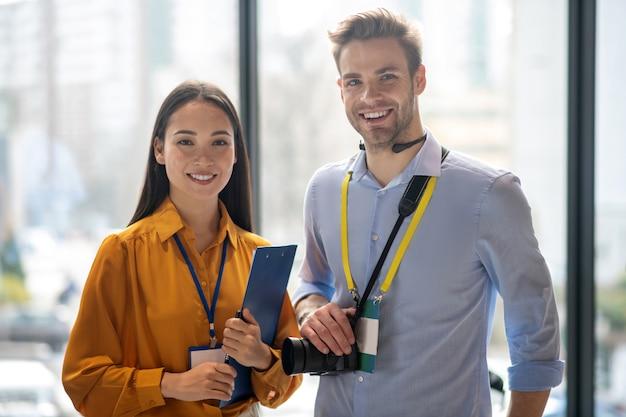 Deux journalistes souriant tout en se sentant heureux après une bonne journée de travail