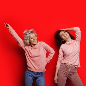 Deux joyeuses dames aux cheveux bouclés pointant et posant