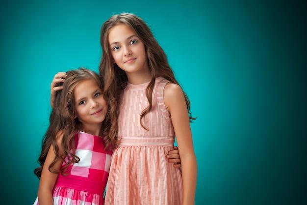 Les deux joyeuses petites filles sur mur bleu