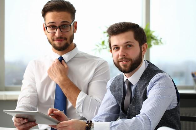 Deux joyeux gestionnaires travaillant au bureau avec pavé tactile
