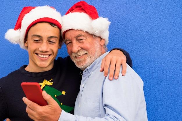 Deux joyeux pères noël contre un mur bleu, un grand-père avec son petit-fils adolescent, sourient en regardant ensemble le téléphone portable. concept de famille moderne et technologique