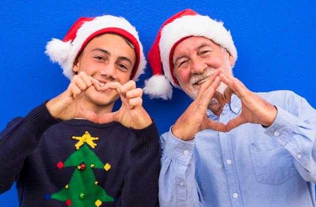 Deux joyeux pères noël, un grand-père avec son petit-fils adolescent, sourient en faisant un cœur avec leurs mains. concept de famille, d'amour et de plaisir