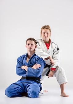 Les deux judokas combattants posant sur gris