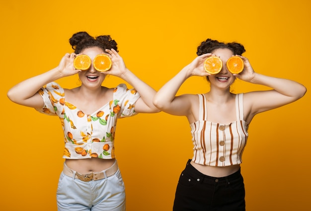 Deux jumeaux caucasiens couvrant son œil d'oranges et sourire sur un mur jaune