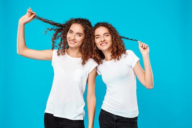 Deux jumeaux de femme tenant les cheveux, souriant au bleu.